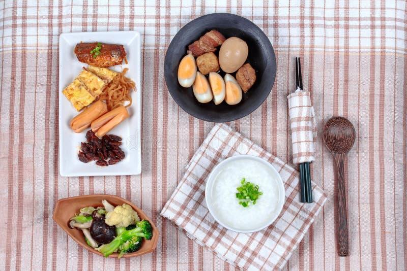 Mingau do arroz com salsicha, os vegetais fritados e o ovo cozido cozido foto de stock royalty free