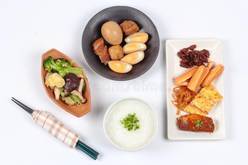 Mingau do arroz com salsicha, os vegetais fritados e o ovo cozido cozido fotos de stock