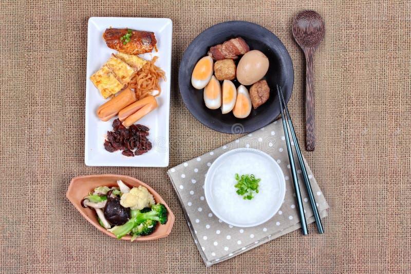 Mingau do arroz do close up com salsicha, os vegetais fritados e o ovo cozido fotografia de stock royalty free