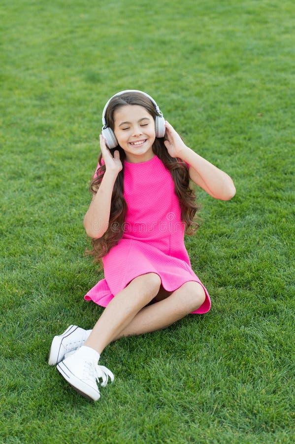 Minha lista de reprodução de verão Ouça música enquanto relaxa ao ar livre podcast educacional Garota desfruta de música verde pr foto de stock
