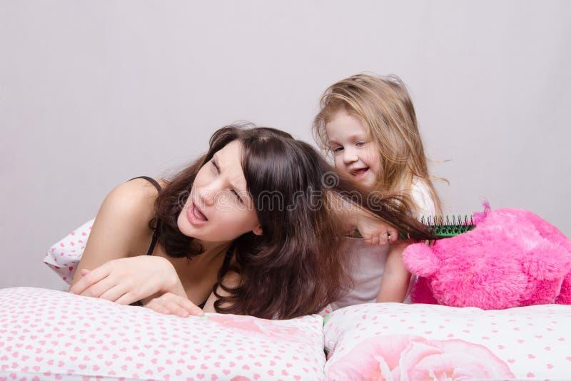 Minha mãe é muito doente Filha que penteia seu cabelo imagens de stock