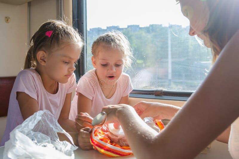 Minha mãe desembala o alimento para crianças com fome no transporte de segunda classe do trem fotografia de stock royalty free