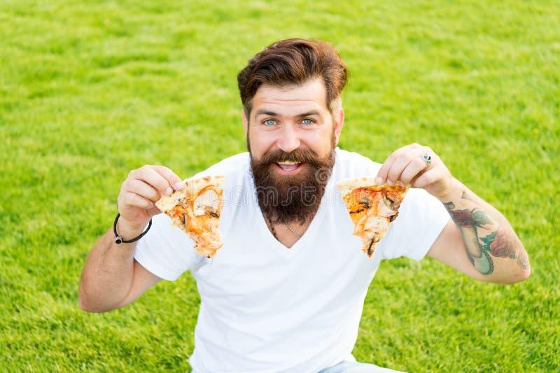 Minha pizza favorita piquenique do verão na grama verde fim de semana da pizza Fast food moderno farpado do homem para comer a pi fotografia de stock royalty free