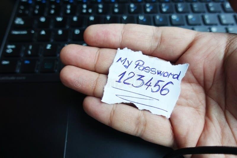Minha senha 123456 na nota de papel guardou pela mão do homem acima do teclado de computador fotografia de stock