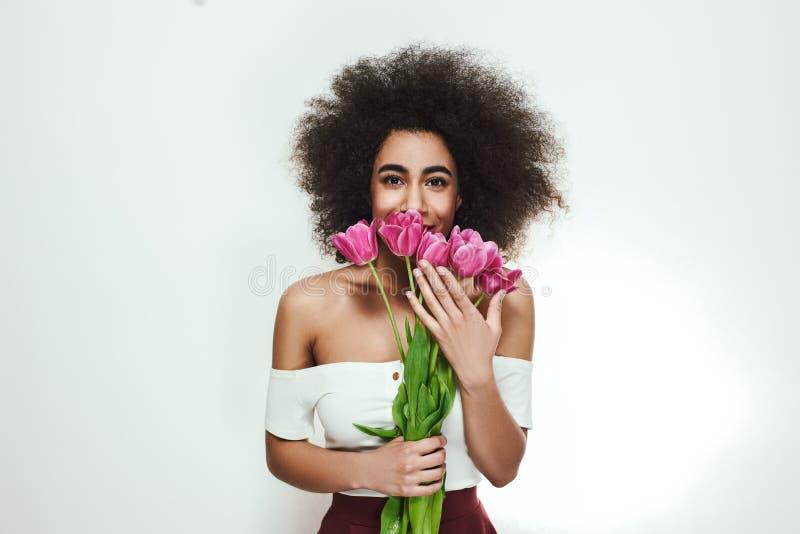 Minhas flores favoritas! A mulher afro-americana bonito e feliz com cabelo encaracolado está guardando tulipas cor-de-rosa fresca imagem de stock