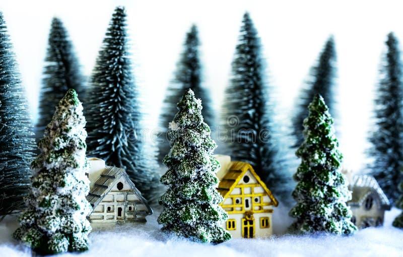 Mini alberi di Natale nevosi con le case nei precedenti delle luci di Bokeh della foresta fotografie stock