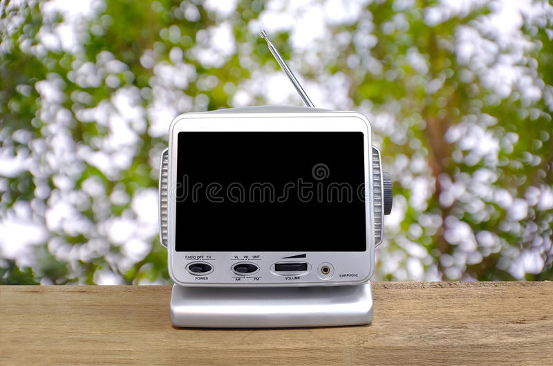 Mini analog television. On wood table under the tree, bokeh blur background stock photos
