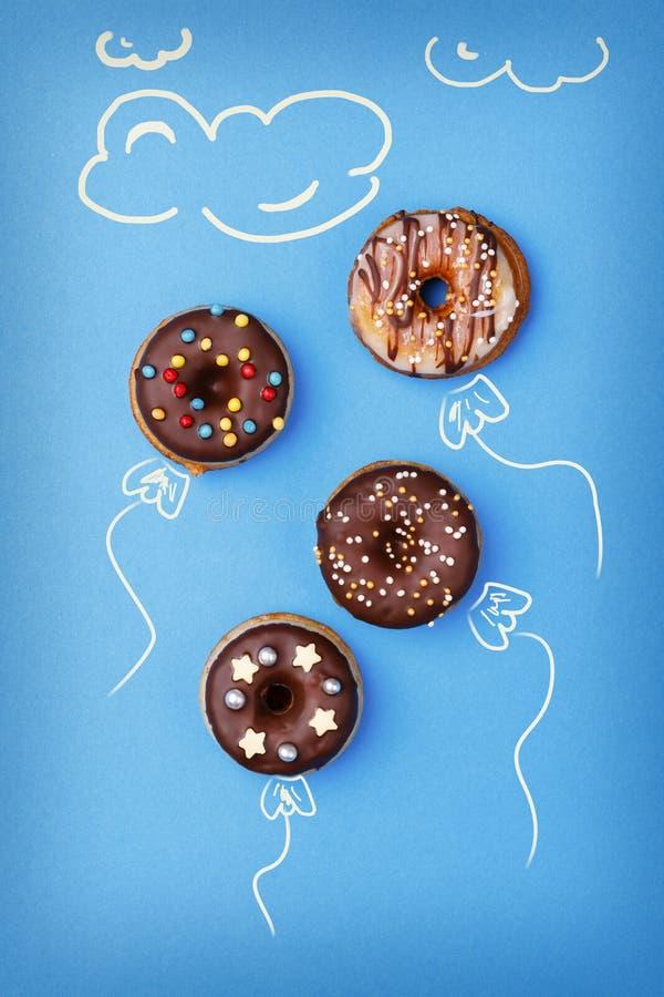 Mini anillos de espuma dulces con el esmalte del chocolade en azul fotos de archivo