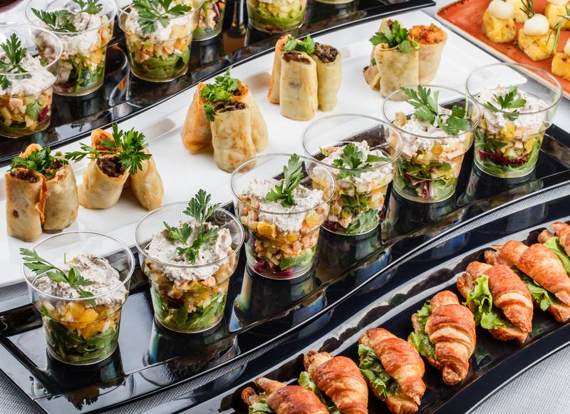 Mini aperitivos com peixes, caviar, queijo, camarão, camarão e verdes dos salmões na tabela de banquete Fim do alimento gourmet a foto de stock royalty free