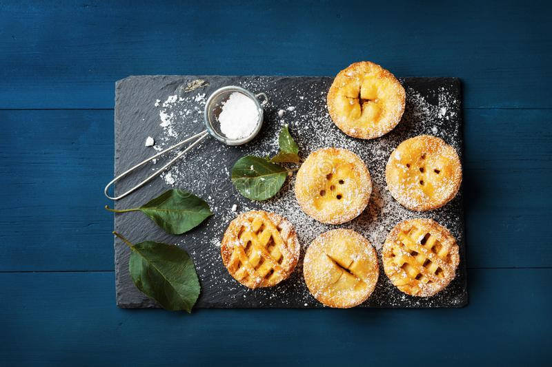Mini apple pies decorated sugar powder on blue table from above. Delicious autumn pastry dessert. royalty free stock image