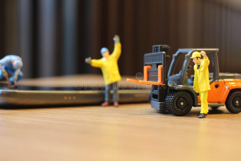 Mini- arbetare som kontrollerar den generiska mobiltelefonen arkivfoto