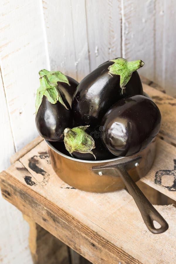 Mini aubergines pourpres dans un plongeur de cuivre sur la boîte en bois de vintage, récolte d'été d'automne photos stock