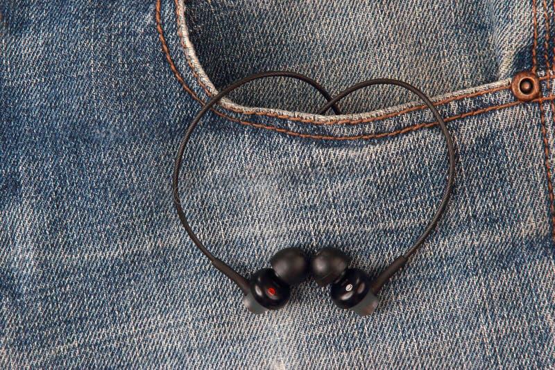 Mini audio headphones in pocket denim pants. The mini audio headphones in pocket denim pants royalty free stock photography