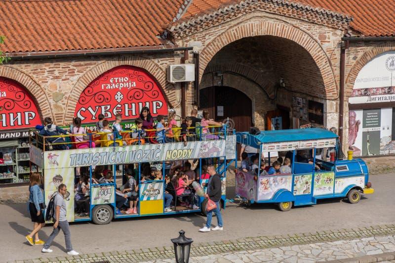 Mini autobusu pi?trowego turystyczny pojazd pe?no turyst?w m?odzi ludzie odwiedza starego ?redniowiecznego fortec? w mie?cie na z zdjęcia stock