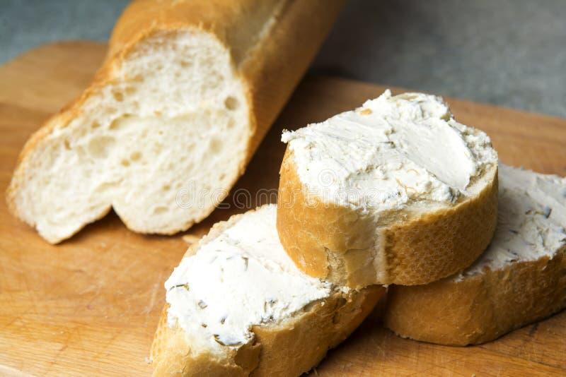 Mini- bagettsmörgåsar med gräddost på skärbrädan royaltyfri fotografi