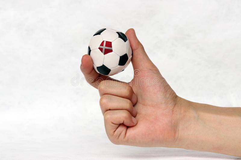 Mini ball of football in hand and one black point is Denmark flag, hold it with two finger on white background. royalty free stock photos
