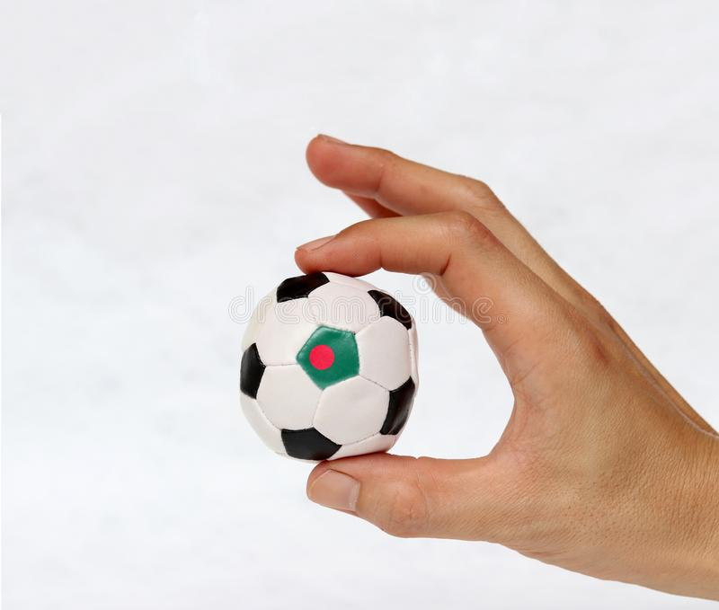 Mini ball of football in hand and one black point of football is Bangladesh flag royalty free stock photo