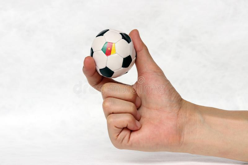 Mini ball of football in hand and one black point of football is Cameroon flag, hold it with two finger on white background stock images