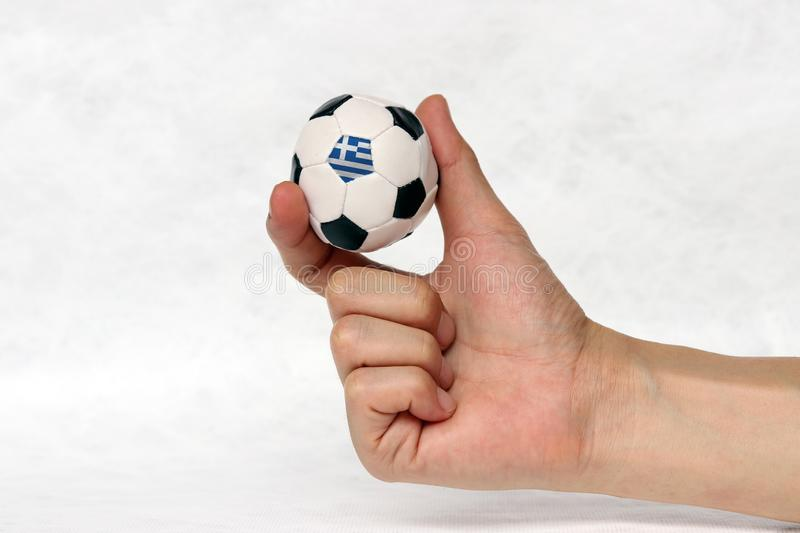 Mini ball of football in hand and one black point of football is Greece flag, hold it with two finger on white background royalty free stock photography
