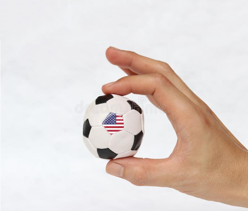 Mini ball of football in hand and one black point of football is United States of America  flag, hold it with two finger on white stock photo