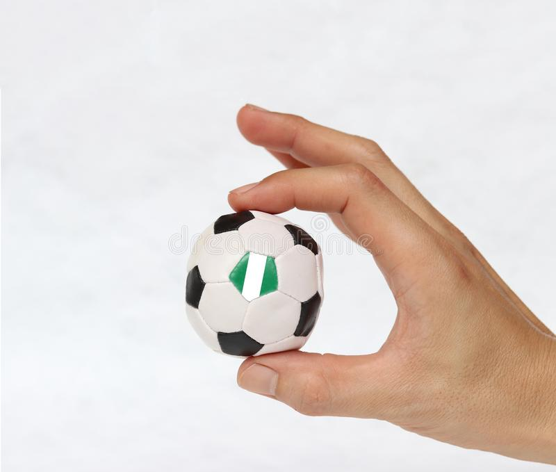 Mini ball of football in hand and one black point of football is Nigeria flag, hold it with two finger on white background stock image