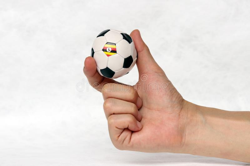 Mini ball of football in hand and one black point of football is Uganda flag, hold it with two finger on white background stock photos