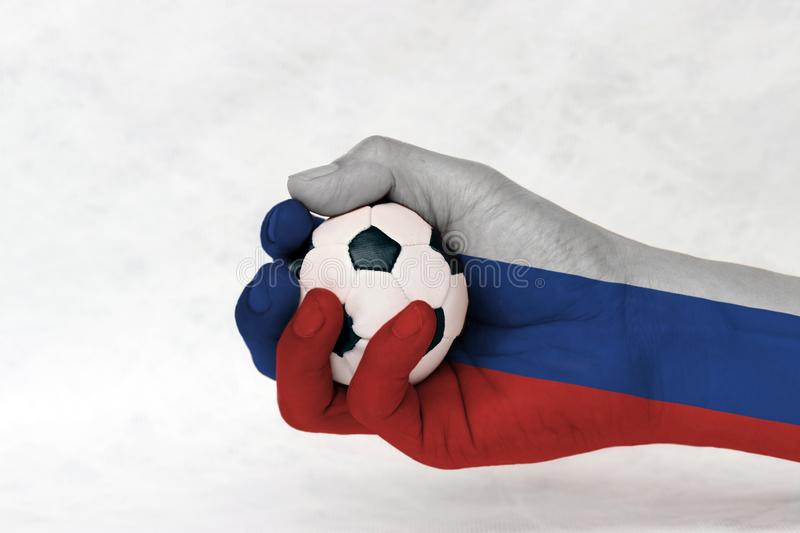 Mini ball of football in Russia flag painted hand on white background. Concept of sport or the game in handle or minor matter. stock images