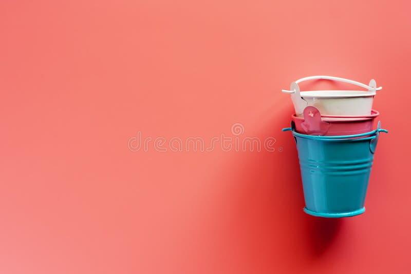 Mini barwioni blaszani pails lub wiadra na różowym tle obrazy royalty free