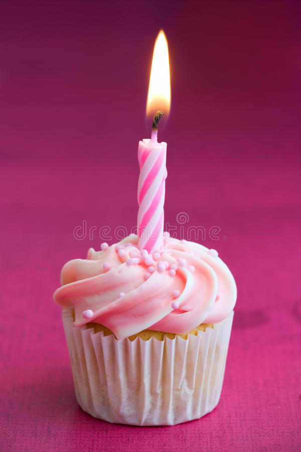 Mini birthday cupcake. Mini cupcake decorated with a single birthday candle stock photography