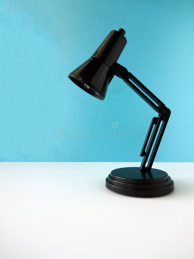 Mini Black Adjustable Lamp. Black Adjustable Toy Lamp against a Blank Blue Background stock photos