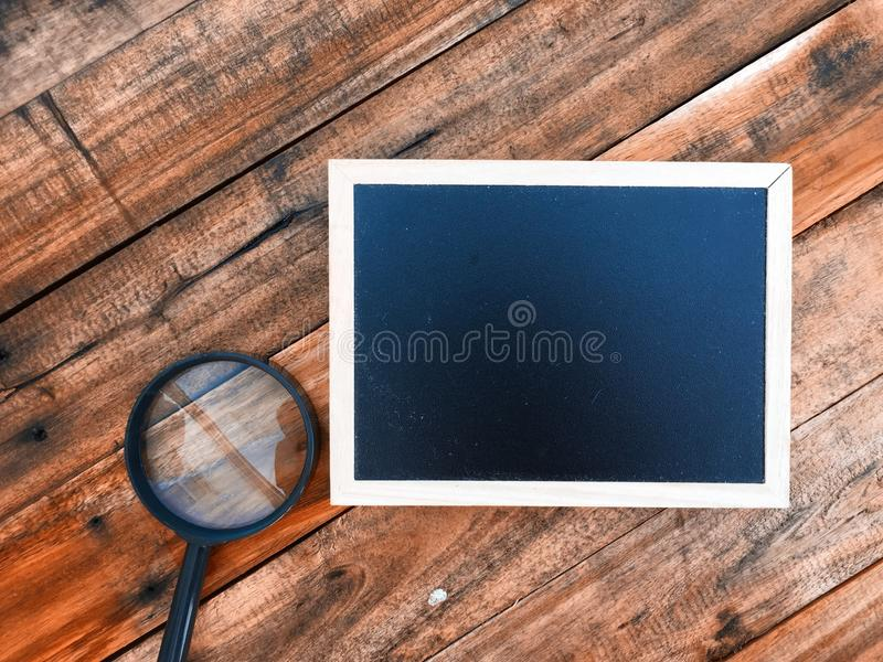 Mini blackboard and magnifier over wooden background royalty free stock photo