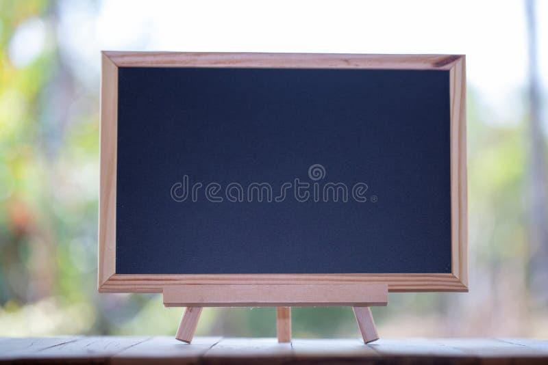 Mini Blank svart tavla på trätabellen med kopieringsutrymme tavla arkivbild