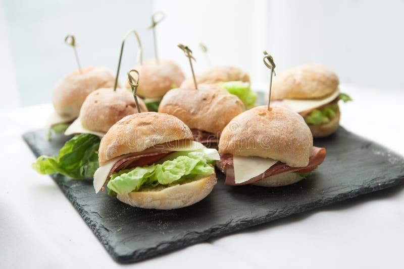 Mini bocadillos con la ensalada, el queso, el tocino y el salami en la placa de piedra fotos de archivo