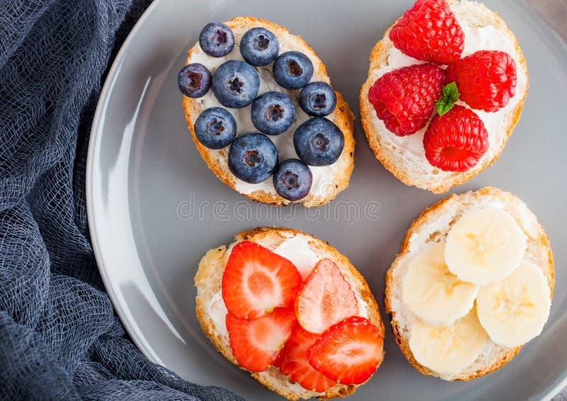 Mini bocadillos sanos frescos con el queso cremoso, las frutas y las bayas en placa gris con el paño Fresas, arándanos, plátanos imagen de archivo libre de regalías