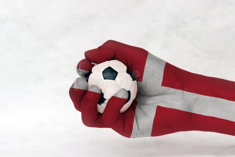 A mini bola do futebol na bandeira de Dinamarca pintou a mão no fundo branco imagem de stock royalty free