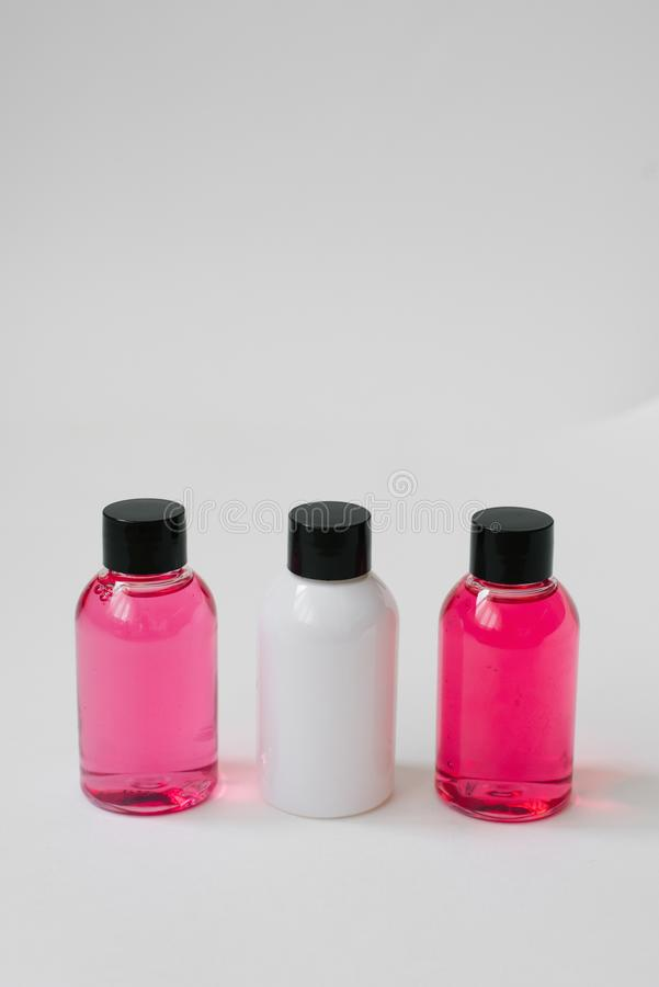 Mini bottles of pink and white color with body care cosmetics or hair on white background. Improvement of the hotel. Copy space royalty free stock photos