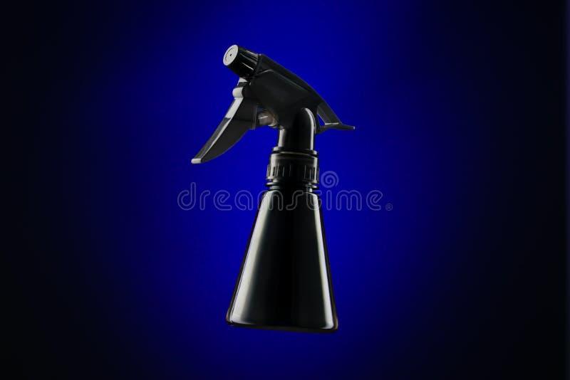 Mini bouteille noire de jet au-dessus de fond bleu photo stock
