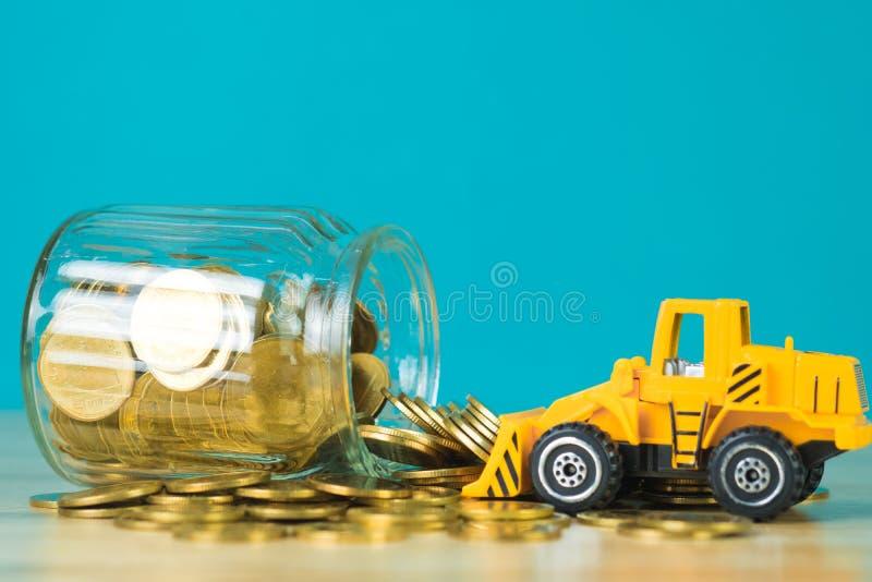 Mini buldożer ciężarówki ładowania sterty moneta z stosem złocista moneta t zdjęcie stock