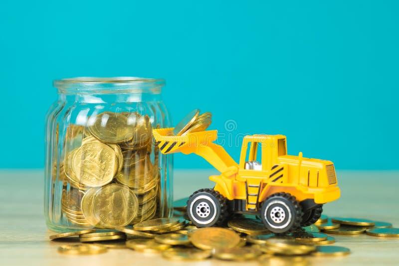 Mini buldożer ciężarówki ładowania sterty moneta z stosem złocista moneta t obrazy royalty free
