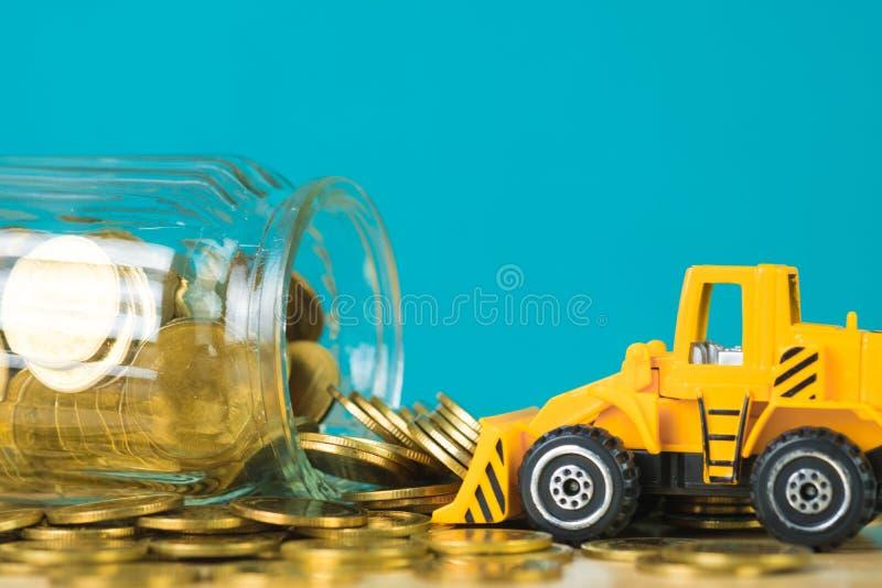 Mini buldożer ciężarówki ładowania sterty moneta z stosem złocista moneta t obraz stock