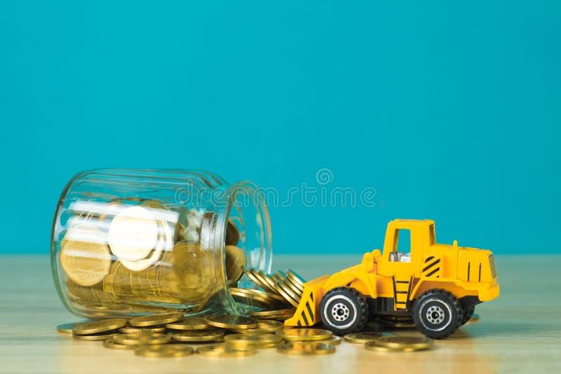 Mini buldożer ciężarówki ładowania sterty moneta z stosem złocista moneta t fotografia royalty free