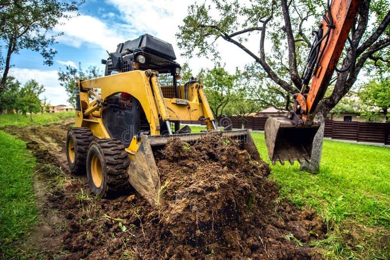mini buldożer pracuje z ziemią, ruszać się glebowy i robić, kształtujący teren pracę obraz stock
