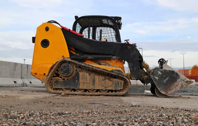 Mini bulldozer su una strada della ghiaia in un cantiere o fotografie stock libere da diritti