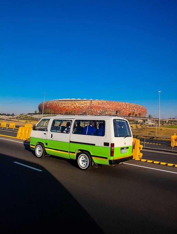 Mini Bus Taxi delante del estadio de fútbol de FNB en Soweto fotografía de archivo libre de regalías