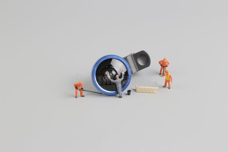 a mini câmera da limpeza do trabalhador dos povos len fotografia de stock