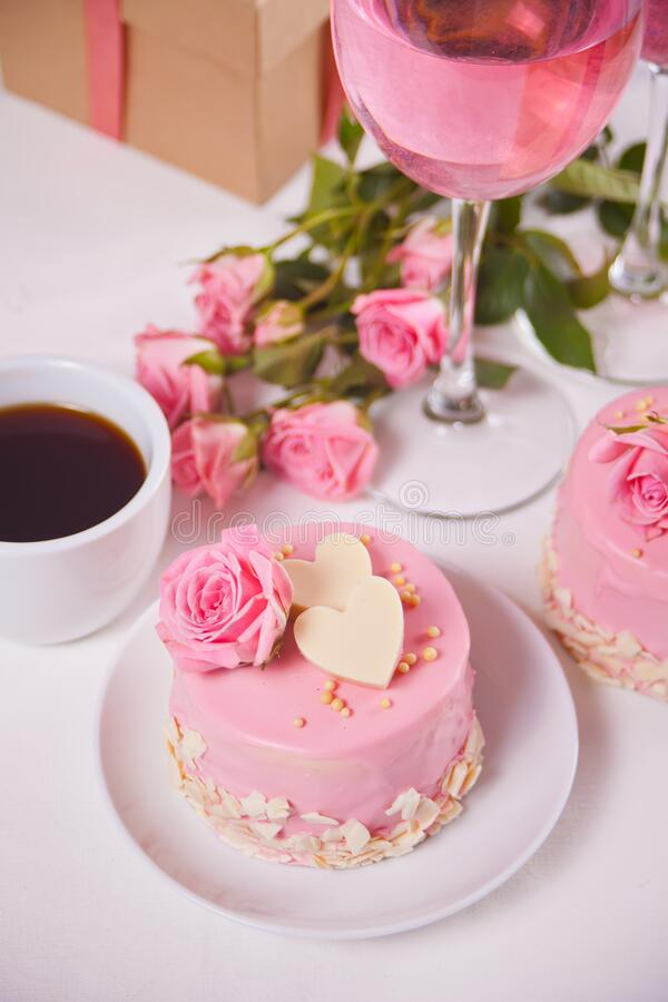 Mini cake with pink glaze, beautiful roses, cup of coffee, glass of pink wine on the white table.  stock photo