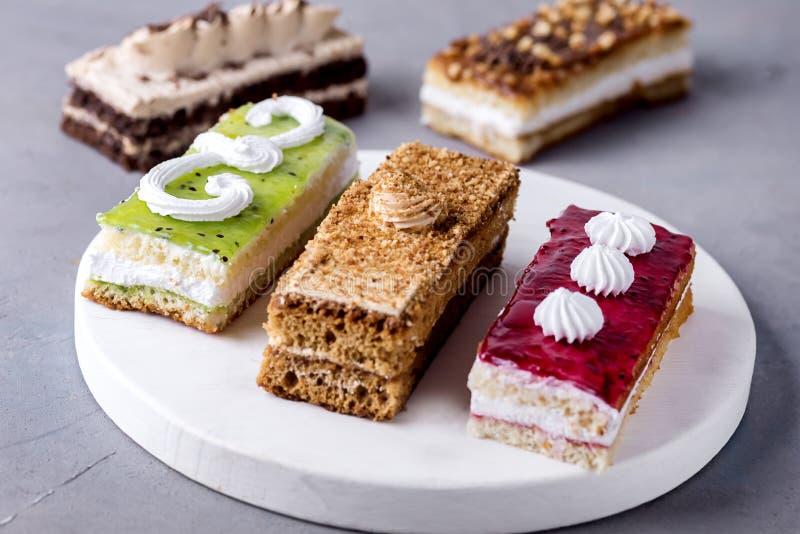 Mini Cakes differente ordinato con il cioccolato crema del caff? ha salato il caramello e le bacche sopra Mini Cakes Dessert sapo fotografia stock libera da diritti