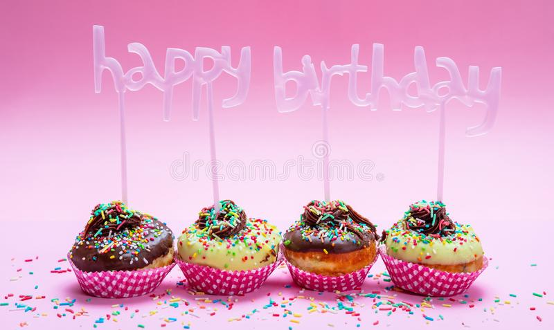 Mini cakes with icing and colorful sprinkles on pink background, text happy birthday decoration royalty free stock image
