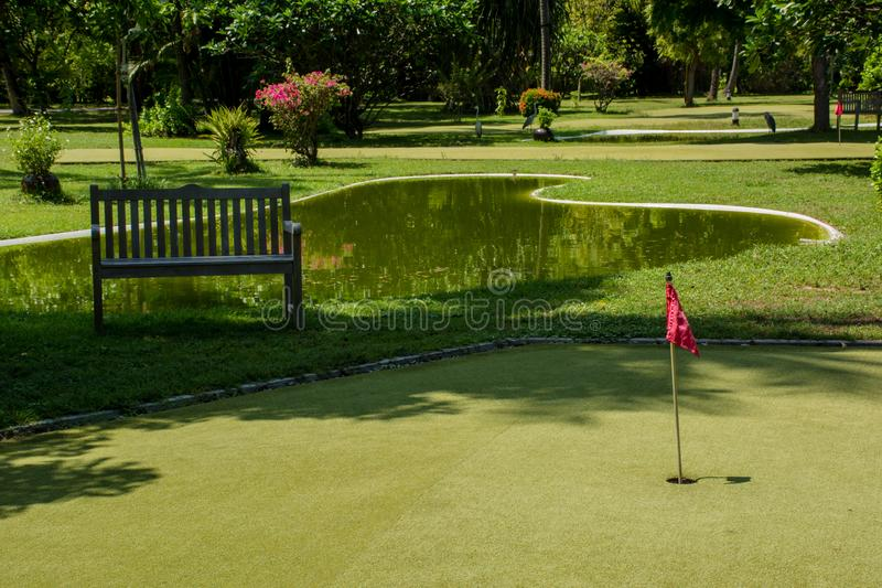 Mini campo del golf con la bandera roja en la isla tropical en Maldivas imagen de archivo