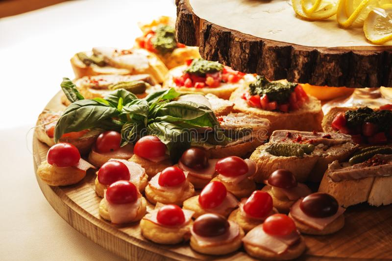 Mini canapes food.Beautiful decorat catering banquet wooden  table. Snacks and appetizers. Wedding celebration royalty free stock image